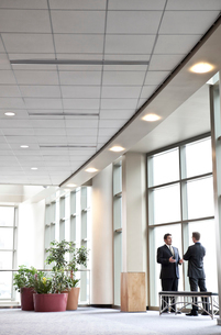 Two businessmen meeting in front of a window in a large convention centre lobby.の写真素材 [FYI02264660]