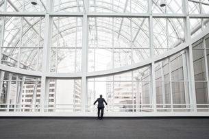 A man standing in an open space in a glass atrium in an office building, leaning on a railing, rearの写真素材 [FYI02264661]