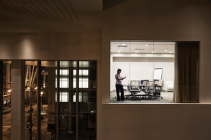 A view looking into a conference room at night of an Asian businesswoman.の写真素材 [FYI02264663]
