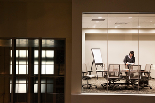 A view looking into a conference room at night of an Asian businesswoman.の写真素材 [FYI02264666]