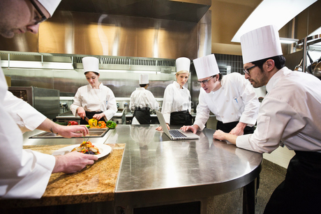 A crew of chef's working in a commercial kitchen, while several chefs wok on a laptop computer.の写真素材 [FYI02264667]