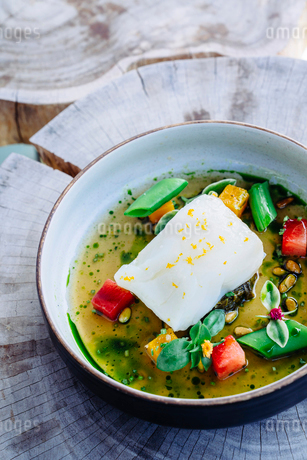Pouring broth on halibut with lemon, peas, melon, beets and herbsの写真素材 [FYI02264668]