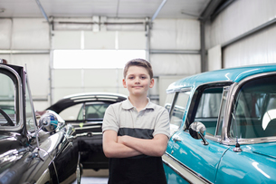 A portrait of a young Caucasian boy in his father's classic car repair shop.の写真素材 [FYI02264688]