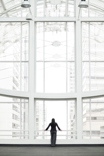 A businesswoman standing at a window in a large convention centre lobby.の写真素材 [FYI02264689]
