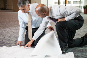 Two men going over plans for a new office space while kneeling on an office carpet.の写真素材 [FYI02264691]