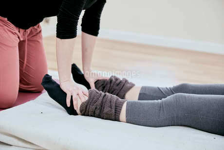 Woman receiving a Thai massage to her feet by a therapist.の写真素材 [FYI02264692]