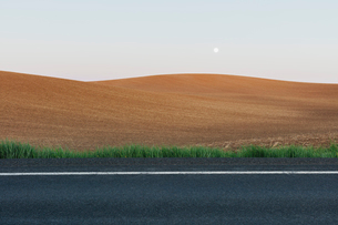 Moonrise over rolling freshly planted fields, road in foregroundの写真素材 [FYI02264693]