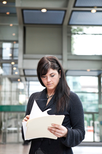 A young Caucasian businesswoman going through paperwork in a convention centre lobby area.の写真素材 [FYI02264694]
