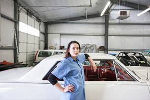 A portrait of a Caucasian female mechanic in a car repair shop.の写真素材 [FYI02264699]