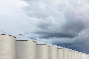 Rows of grain silos, stormy skies in distance, Saskatchewan, Canada.の写真素材 [FYI02264705]