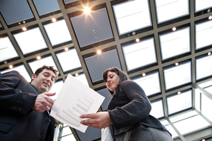 Two business people going over paperwork in a large convention centre lobby.の写真素材 [FYI02264707]