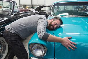 A Caucasian male hugging the hood of his old sedan in a classic car repair shop.の写真素材 [FYI02264708]