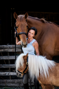 Woman standing outside a stable, holding a brown bay horse and a small Shetland pony by their reins.の写真素材 [FYI02264712]