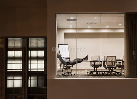 A view looking into a conference room at night  with a single businessman at a conference table.の写真素材 [FYI02264714]