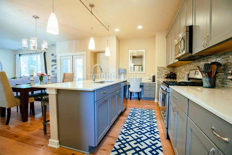 Modern home kitchen diner with green grey fitted units, a kitchen island and blue floor rug.の写真素材 [FYI02264716]