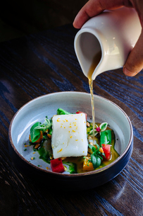 Pouring broth on halibut with lemon, peas, melon, beets and herbsの写真素材 [FYI02264720]