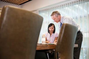 An Asian businesswoman and a Caucasian businessman at work at a conference table.の写真素材 [FYI02264722]