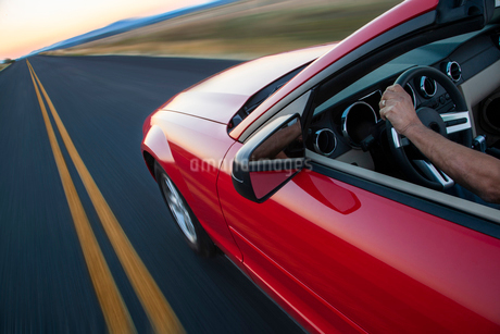 A view looking down from behind of a hand on a steering wheel of a convertible sports car moving onの写真素材 [FYI02264724]