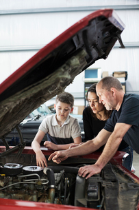 A senior Caucasian male car mechanic talks to a Caucasian mother and her son about a engine repair iの写真素材 [FYI02264725]