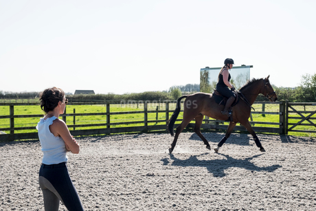 Woman, a horse trainer watching a young woman riding on a brown bay horse in a schooling ring.の写真素材 [FYI02264728]