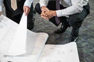 Closeup of two men going over plans for a new office space while kneeling on an office carpet.の写真素材 [FYI02264731]