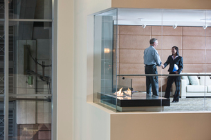 A large building, lobby, view looking into an office with glass walls, two business people talking.の写真素材 [FYI02264734]