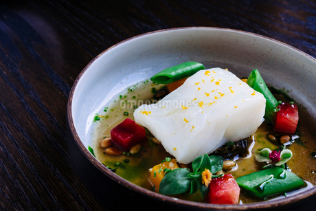 Pouring broth on halibut with lemon, peas, melon, beets and herbsの写真素材 [FYI02264735]