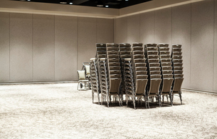Stacked chairs in an empty convention centre meeting room.の写真素材 [FYI02264738]