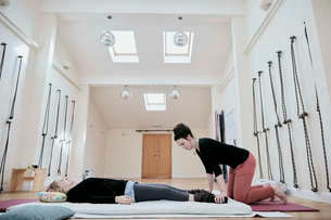 Woman lying down fully clothed having a Thai massage in a light filled exercise studioの写真素材 [FYI02264742]