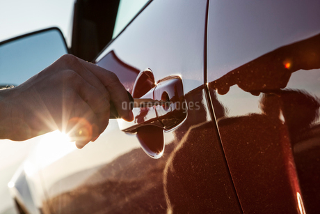 A closeup of a hand putting a key in the door of an automobile.の写真素材 [FYI02264743]