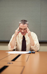 A Caucasian businessman sitting at a desk showing the stress of work.の写真素材 [FYI02264745]