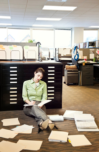 A young Caucasian businesswoman sitting on the floor of her office going over paperwork.の写真素材 [FYI02264746]