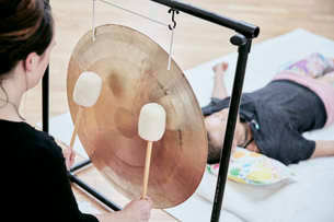 Woman striking a large gong with soft drumsticks during a sound therapy sessionの写真素材 [FYI02264763]