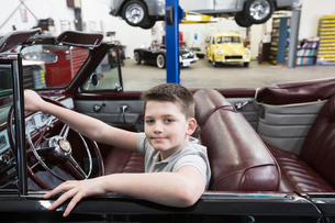 A young Caucasian boy at the wheel of an old convertible in his dad's classic car repair shop.の写真素材 [FYI02264770]