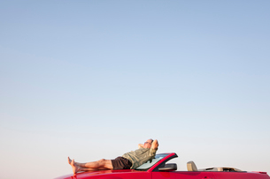 Caucasian male relaxing on the hood of his convertible sports car.の写真素材 [FYI02264771]