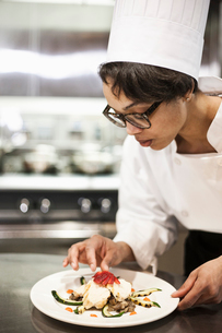 A black female chef working in a commercial kitchen,の写真素材 [FYI02264777]