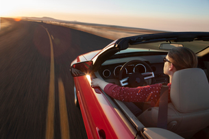 A view from above looking down on a Caucasian woman driving a convertible sports car.の写真素材 [FYI02264786]