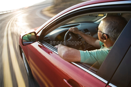 A senior Hispanic man at the wheel of his sedan with an ear piece for communications.の写真素材 [FYI02264788]