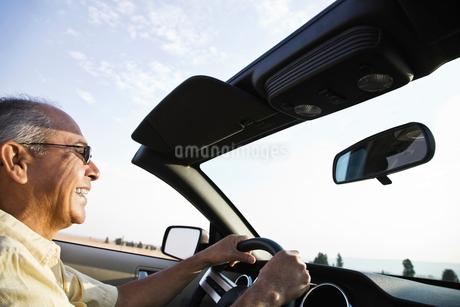 An Hispanic senior man laughing and driving his convertible sports car.の写真素材 [FYI02264813]