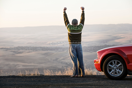 Caucasian male celebrating with his arms n the air standing next to his car at a rest stop near Lewiの写真素材 [FYI02264820]