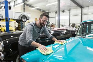 A Caucasian male car mechanic applying wax to the hood of an old sedan in his classic car repair shoの写真素材 [FYI02264829]