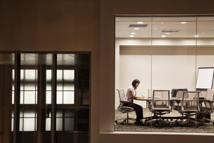 A view looking into a conference room at night of an Asian businesswoman.の写真素材 [FYI02264832]