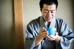 Japanese man wearing traditional kimono holding blue tea bowl during tea ceremony.の写真素材 [FYI02264834]
