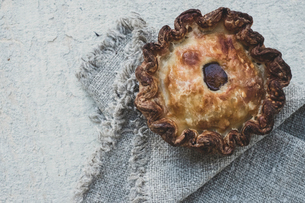 High angle close up of a freshly baked raised Pork Pie on a grey fabric napkin.の写真素材 [FYI02264837]