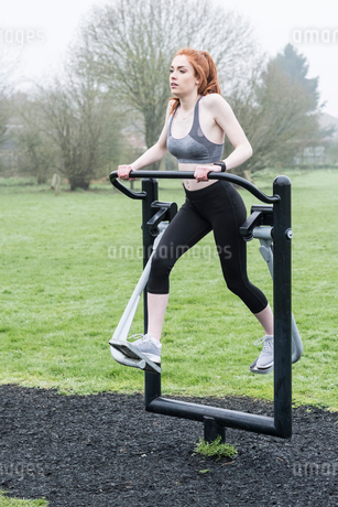 Young woman with long red hair wearing sports kit, using outdoor exercise machine.の写真素材 [FYI02264850]