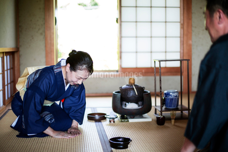Japanese woman wearing traditional bright blue kimono with cream coloured obi and man kneeling on flの写真素材 [FYI02264856]