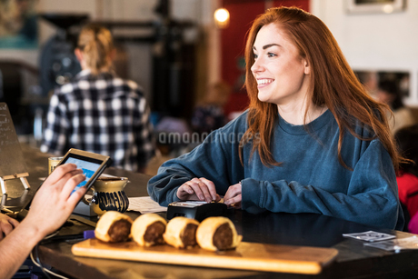 Smiling young woman with long red hair standing at a counter in a restaurant, paying her bill.の写真素材 [FYI02264858]