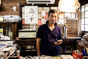 Japanese man standing in a Washi producing workshop holding a smart phone, smiling at camera.の写真素材 [FYI02264861]