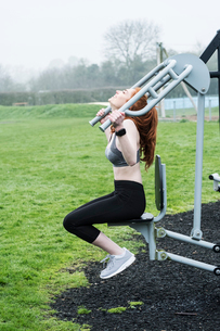 Young woman with long red hair wearing sports kit, using outdoor exercise machine.の写真素材 [FYI02264870]