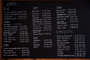 Close up of blackboard with handwritten list of cheese and charcuterie products in a delicatessen.の写真素材 [FYI02264871]